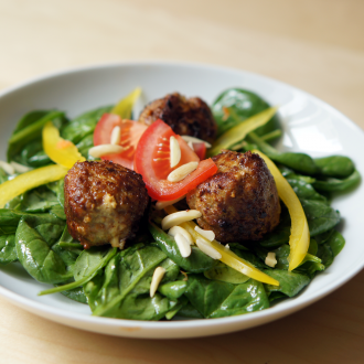 Fleischbällchen auf frischem Blattspinat-Salat